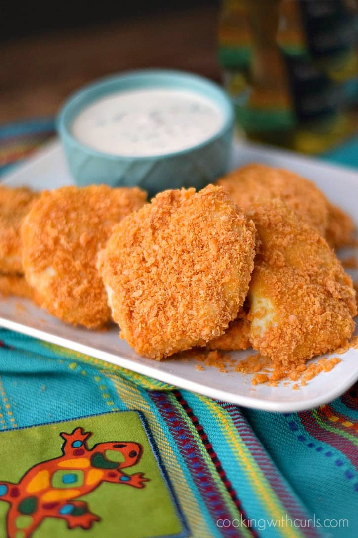 cheeze-it covered chicken tenders on a white plate with a small bowl of bacon ranch dressing