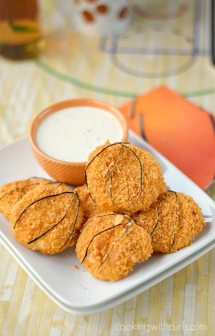 cheez-it baked chicken tenders shaped to look like basketballs stacked on a square white plate surrounding an orange bowl of ranch dressing