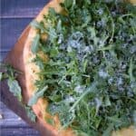 Pizza topped with pesto, arugula, and grated parmesan cheese with title graphic across the top.