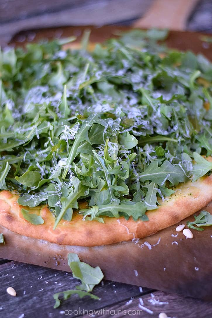 Pizza topped with pesto, arugula, and grated parmesan cheese close-up.