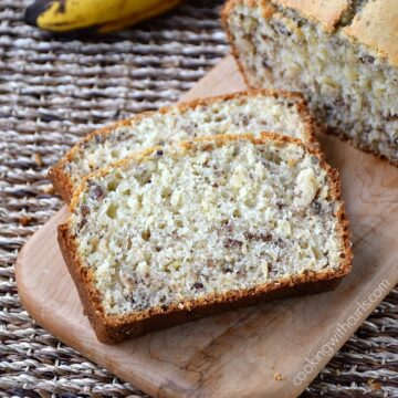 Banana Nut Bread slices on a wood cutting board with bananas in the background
