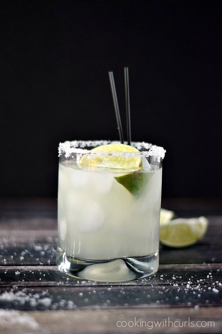 Classic Margarita on the rocks with lime wedges and black straws on a wooden backdrop in front of a black background