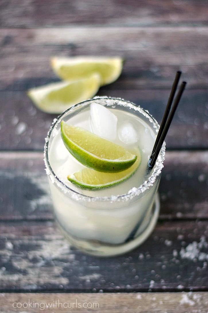 classic margarita in a small glass with two lime wedges and two black straws on a wooden board with two lime wedges in the background