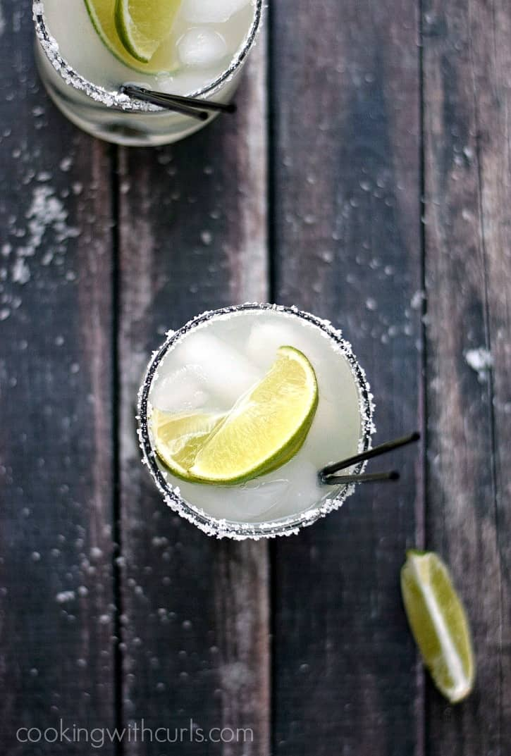two classic margaritas on the rocks with lime wedges and black straws on a wooden background