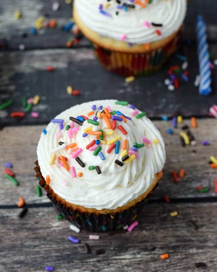 Homemade Funfetti Cupcakes on a wooden background with sprinkles everywhere