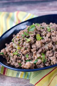 Italian Seasoned Ground Beef in a large, blue bowl sitting on a striped napkin