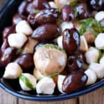 marinated mushrooms, olives, and mozzarella pearls in a dark blue oval bowl