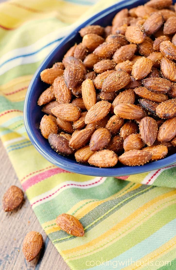 an oval blue bowl sitting on a striped napkin filled with almonds