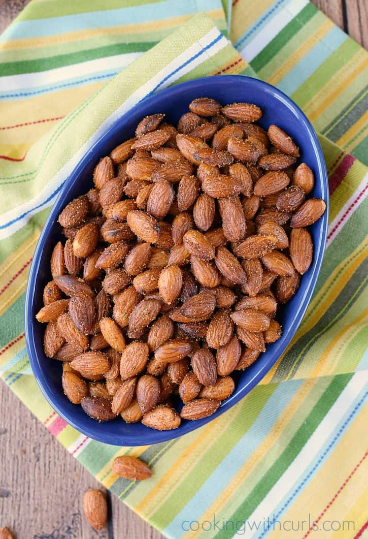 sweet and spicy almonds in an oval blue bowl sitting on a striped napkin