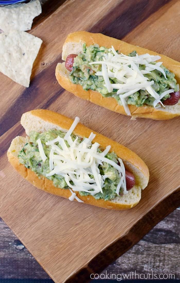 two hot dogs in buns topped with guacamole and shredded cheese sitting on a wooden board