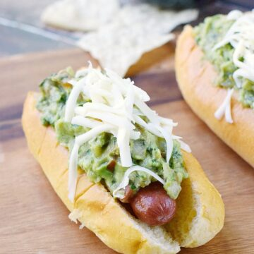 two hot dog buns sitting on a wooden board filled with a hot dog and guacamole, topped with shredded cheese with tortilla chips in the back ground