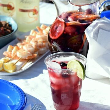 a clear plastic cup filled with berries and sangria surrounded by cilantro lime shrimp, a pitcher of sangria, blue plates and bottles of wine