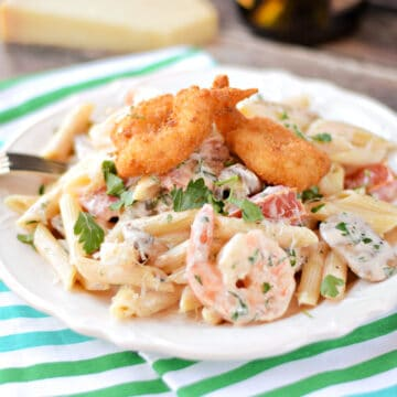 Penne pasta mixed with a creamy shrimp sauce, shrimp, mushrooms, tomatoes, and topped with three breaded shrimp on a white plate.