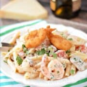 Penne pasta mixed with a creamy shrimp sauce, shrimp, mushrooms, tomatoes, and topped with three breaded shrimp on a white plate with title graphic across the top.