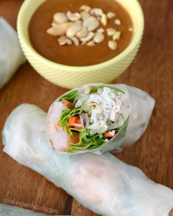 spring rolls laying on a wooden board with a diagonal cut half laying on top and a yellow bowl of peanut sauce in the left corner