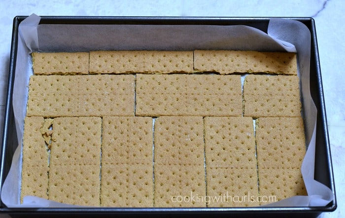 Graham crackers cover the bottom of a parchment lined 9 by 13 baking pan.