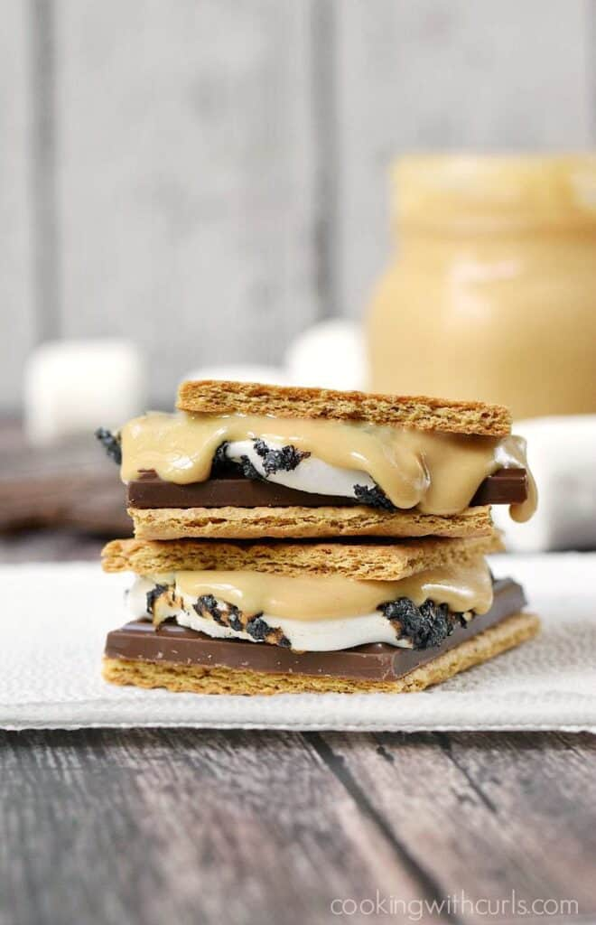 two peanut butter topped smores stacked on top of each other sitting on a paper napkin