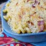 Chipotle Bacon Macaroni and Cheese with crispy panko topping in a blue serving bowl sitting on a red colorful napkin.