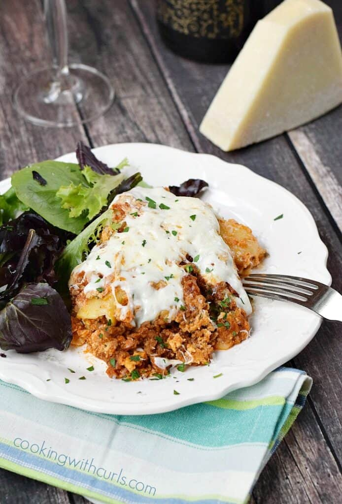 a slice of lasagna on a large white plate with salad on the side and a wedge of Parmesan cheese in the background