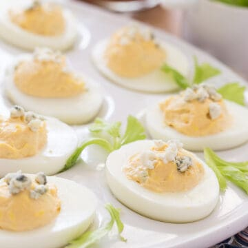 buffalo style eggs topped with blue cheese crumbles and surrounded by celery leaves on a white egg platter