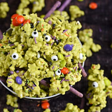A bowl overflowing with green candy coated popcorn, sprinkles, purple pretzel sticks, and multi-colored candy coated chocolates.