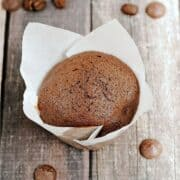 Two chocolate muffins in white paper liners surrounded by coffee beans and dark chocolate chips with title graphic across the top.