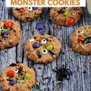 Seven cookies topped with candy eyes, M&M's, and colorful sprinkles surrounded by sprinkles, a black spider, and a glass of milk with title graphic across the top.