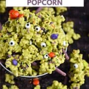 A bowl overflowing with green candy coated popcorn, sprinkles, purple pretzel sticks, and multi-colored candy coated chocolates with title graphic across the top.
