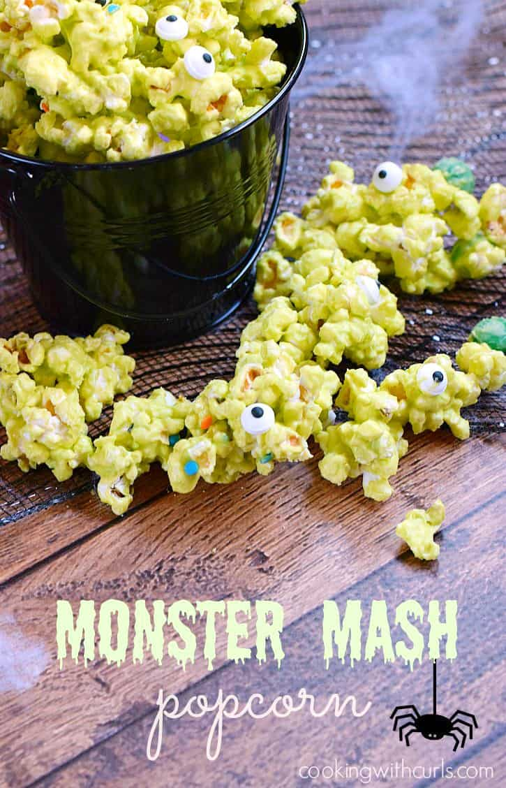 A black bucket overflowing with green popcorn with silly eyes and colored sprinkles surrounded by spider webs