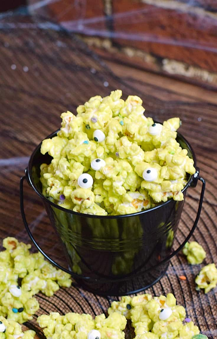 A black bucket overflowing with green monster mash popcorn