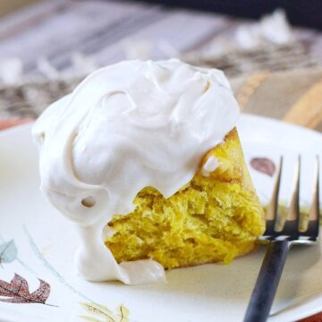a pumpkin cinnamon roll topped with cream cheese frosting on a plate with fall leaves and a spiral black fork on the side