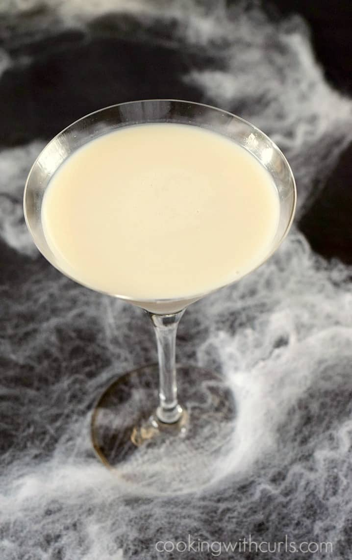 looking down on a martini glass filled with a liquefied ghost martini surrounded by fake spider webs on a black background