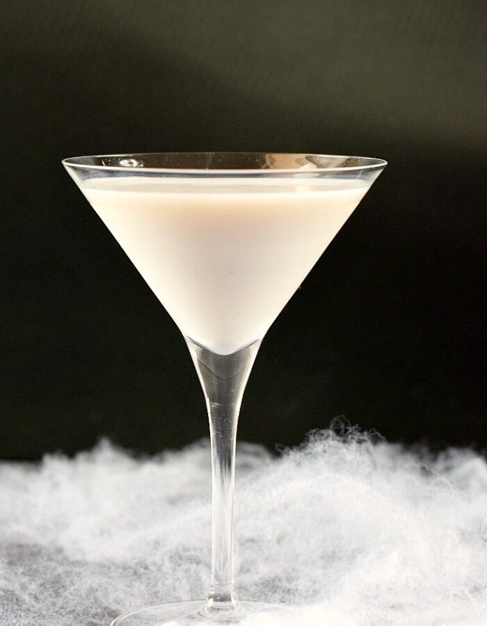Liquefied Ghost Martini in a martini glass surrounded by fake spider webs with a black background