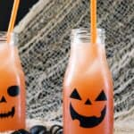 beige netting draped over a black background with two glass bottles decorated with jack o lantern faces, filled with orange cocktails and orange straws