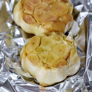 Two bulbs of Roasted Garlic on foil.