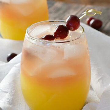 two small, clear glasses with orange on the bottom and peach colored on the top filled with ice cubes and garnished with cranberries on a bamboo stick