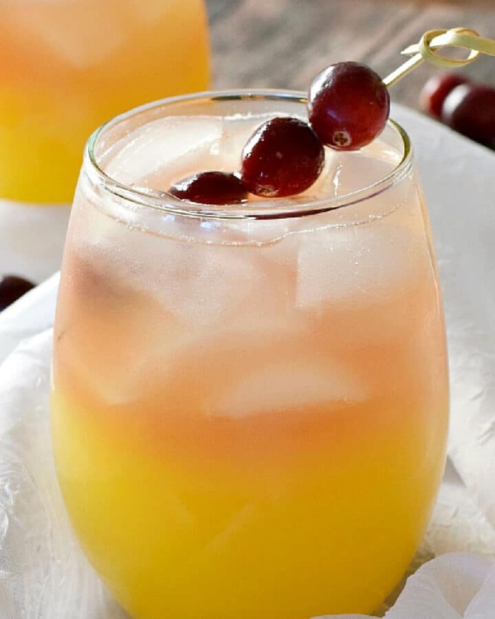 two small, clear glasses with orange on the bottom and peach colored on the top filled with ice cubes and garnished with cranberries on a bamboo stick.