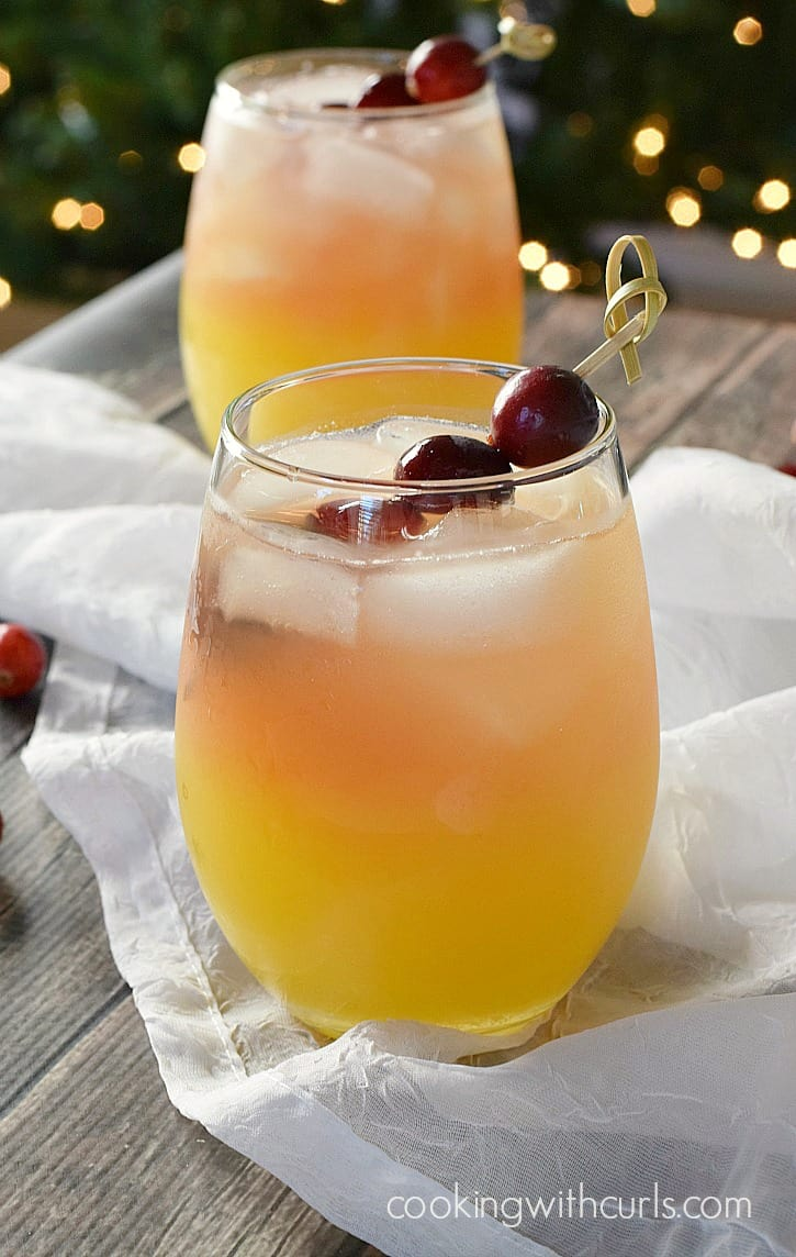 two clear glasses filled with orange, pineapple and cranberry juice garnished with fresh cranberries on a bamboo stick with a lit Christmas tree in the background
