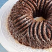 Dark brown bundt cake with decorative design on a white cake plate with title graphic across the bottom.