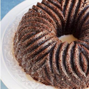 Dark brown bundt cake with decorative design on a white cake plate.