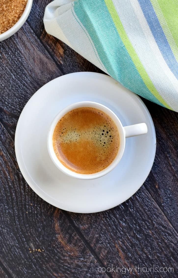 small white cup of perfect espresso next to a colorful striped napkin