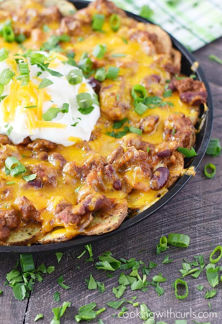 a cast iron skillet filled with potato slices topped with chili and cheese with sour cream in the center and sprinkled with green onions