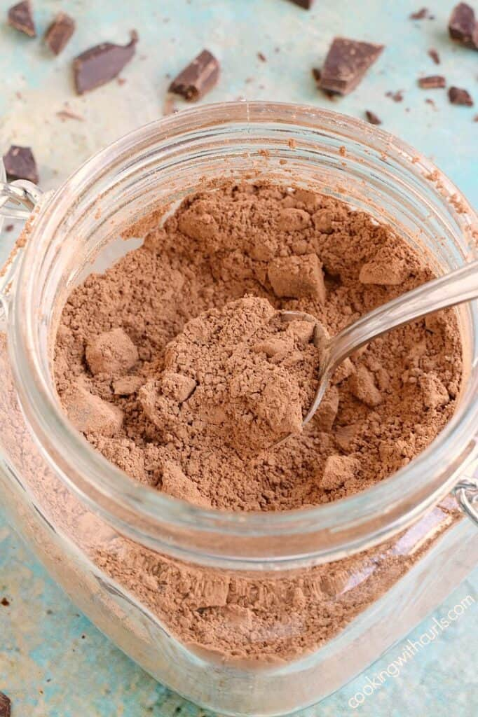 a square glass canister filled with cacao mix with a spoon sticking out the right side and chocolate chunks scattered around the jar