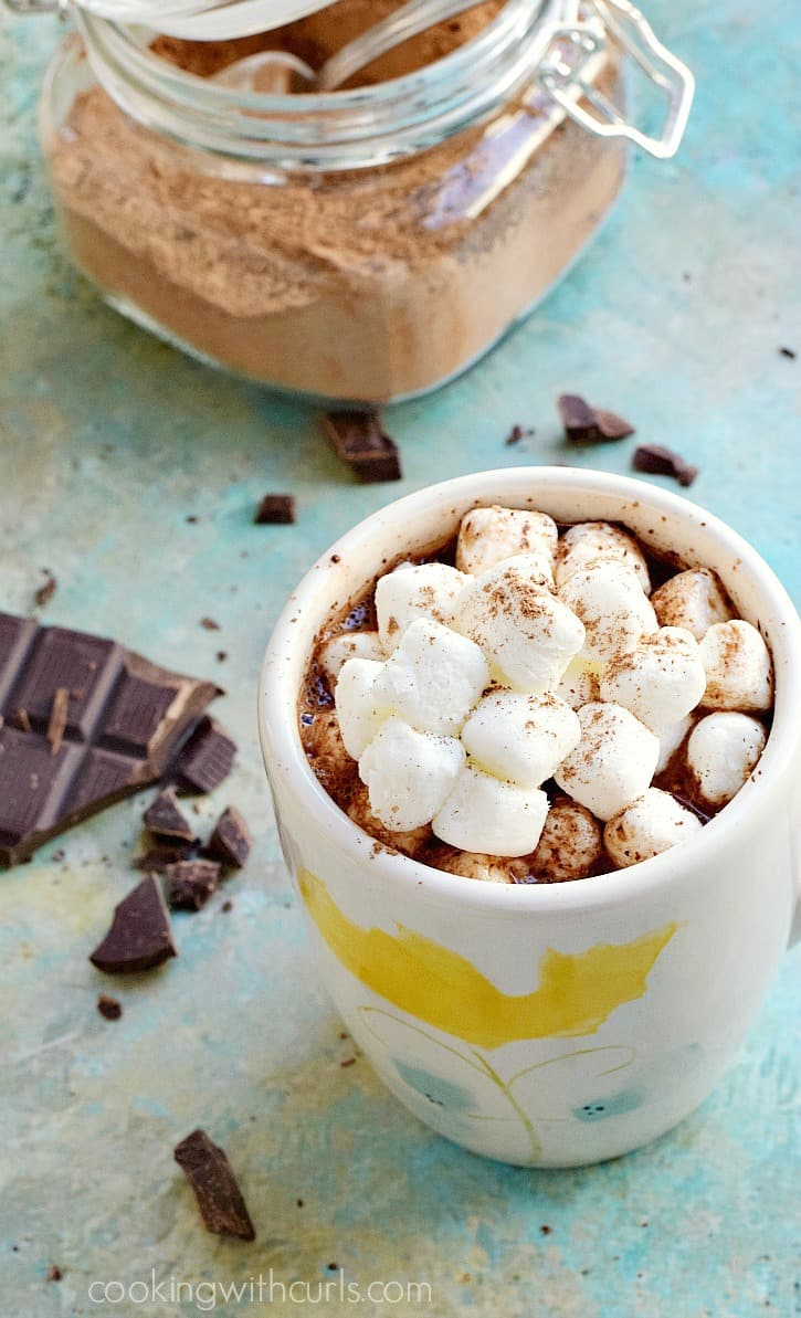 hot cacao topped with mini marshmallows in a floral design cup surrounded by chocolate chunks and a glass jar filled with cacao mix