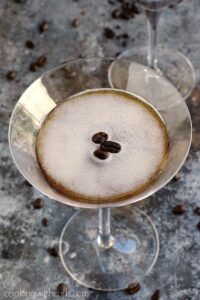 espresso martini in a martini glass with scattered coffee beans around the base
