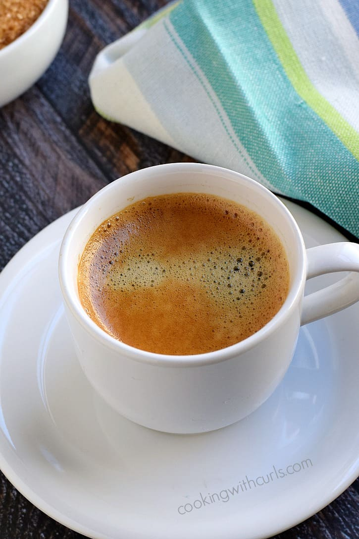 small white cup on a saucer filled with espresso