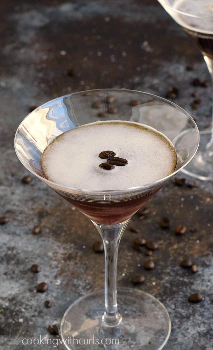 an espresso martini in a martini glass with three coffee beans floating in the center