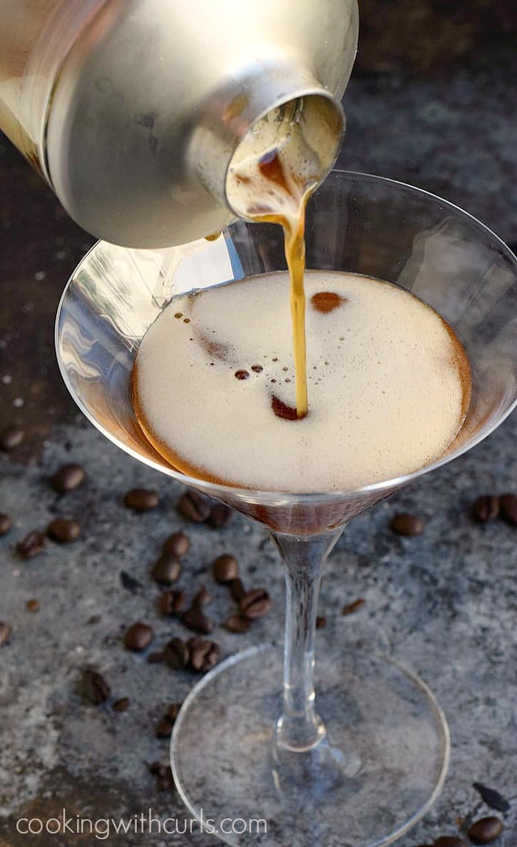 a silver cocktail shaker pouring an espresso martini into a martini glass