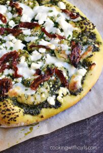 This Shrimp Pesto Pizza is topped with kale pesto, sun-dried tomatoes, feta and mozzarella cheese on a homemade crust cookingwithcurls.com