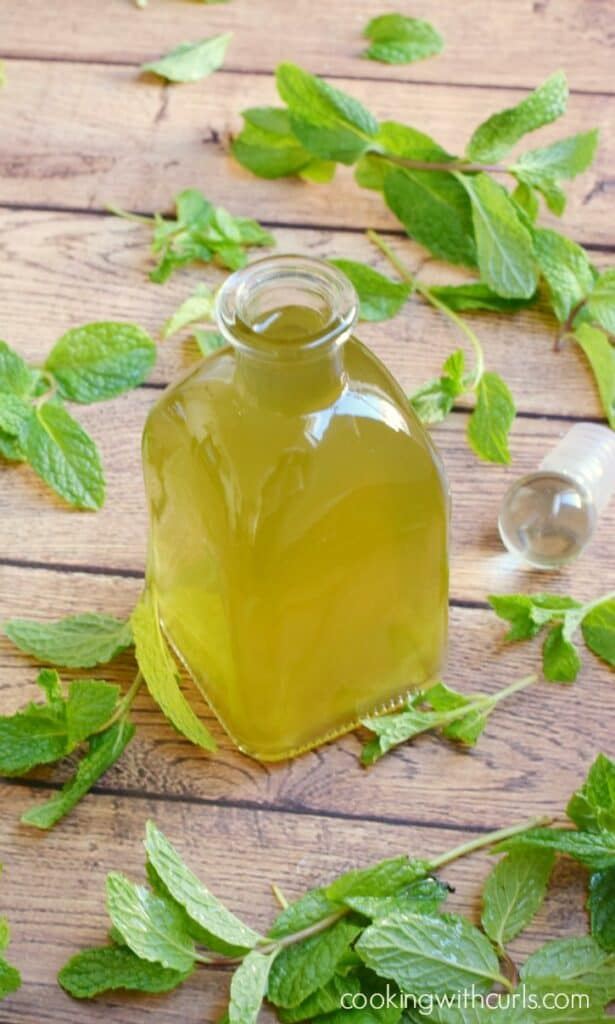 a square glass bottle of peppermint syrup surrounded by french mint sprigs on a wooden background